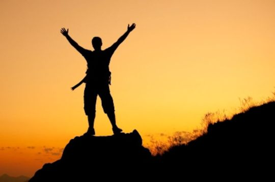 Silhouette of a man on a rock , at sunset, with the arms wide open.